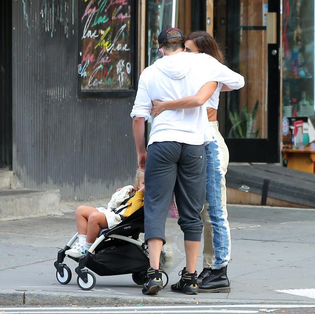画像: 子供の世話をバトンタッチするときに挨拶のハグをするイリーナとブラッドリー。