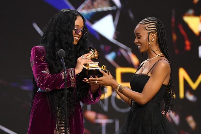 画像: 最優秀楽曲賞のトロフィーを受け取るH.E.R.と、「I Can't Breathe」を共作したティアラ・トーマス。