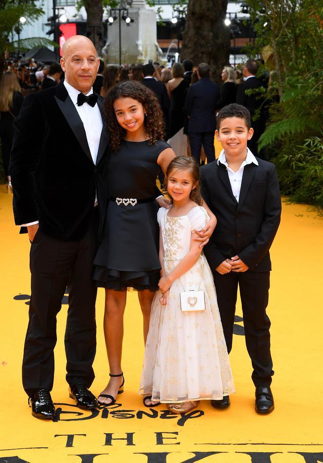 画像: 2019年、ディズニー実写版映画『ライオン・キング』のロンドンプレミアに子どもたちを同伴したヴィン。左から、第1子のハニア、第3子のポーリーン、第2子のヴィンセント。ポーリーンの名前は今は亡き『ワイスピ』共演者にして親友のポール・ウォーカーにちなんでつけられた。
