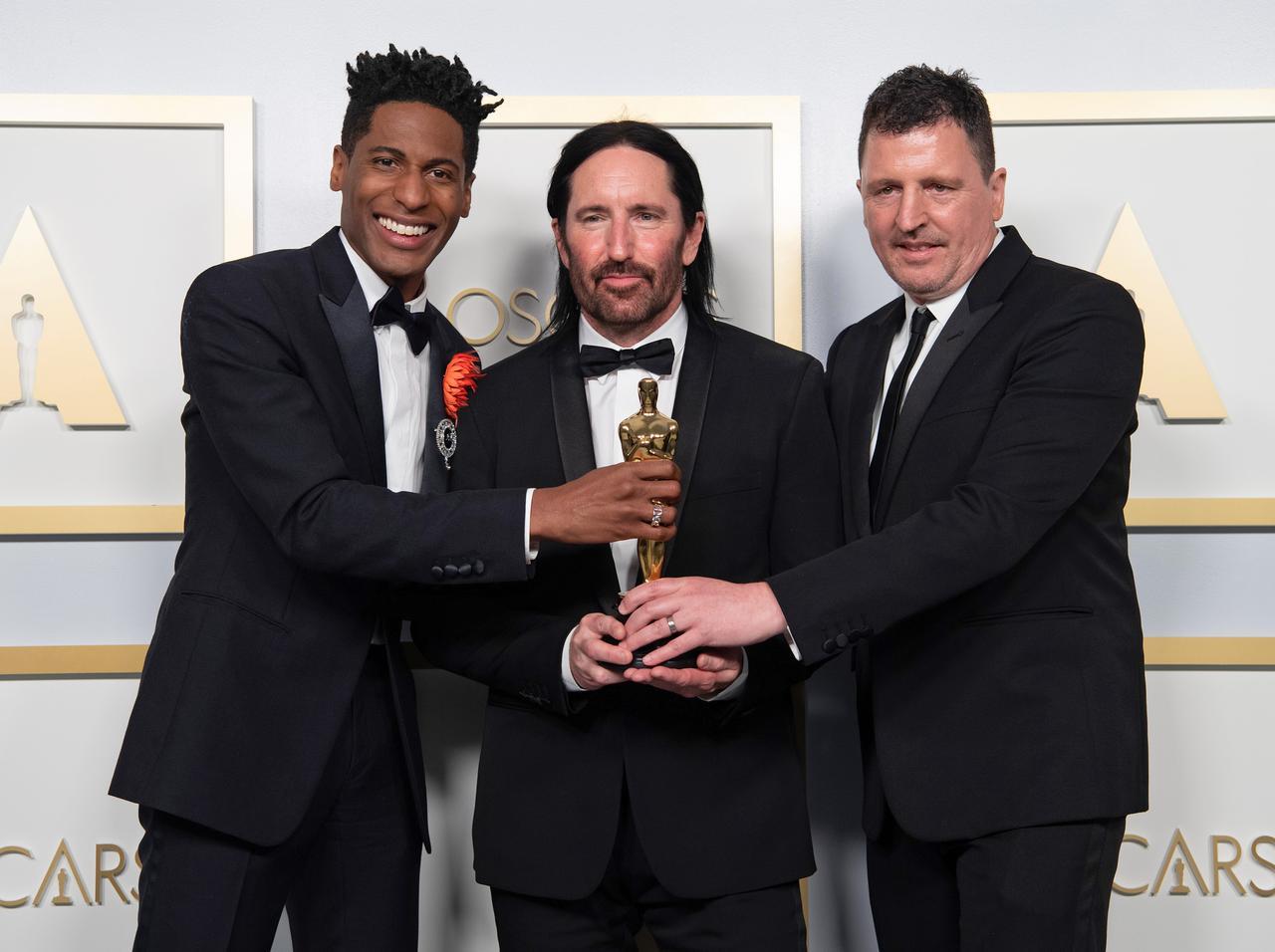 画像: 今年の第93回グラミー賞にて、ジョン・バティステ(左)と共に作曲賞を受賞したトレント・レズナー(中央)とアッティカス・ロス(右)。