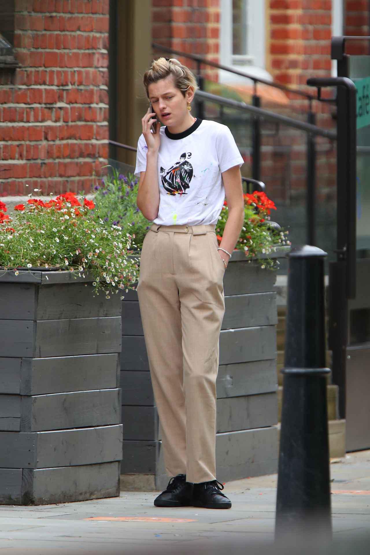 画像2: エマ・コリン、オールバックで電話中