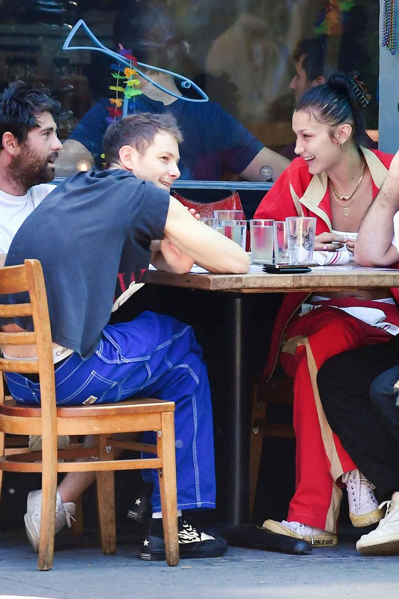 画像: ニューヨークのレストランで男友達2人と過ごすベラとマーク(手前のブルーのパンツの男性)。