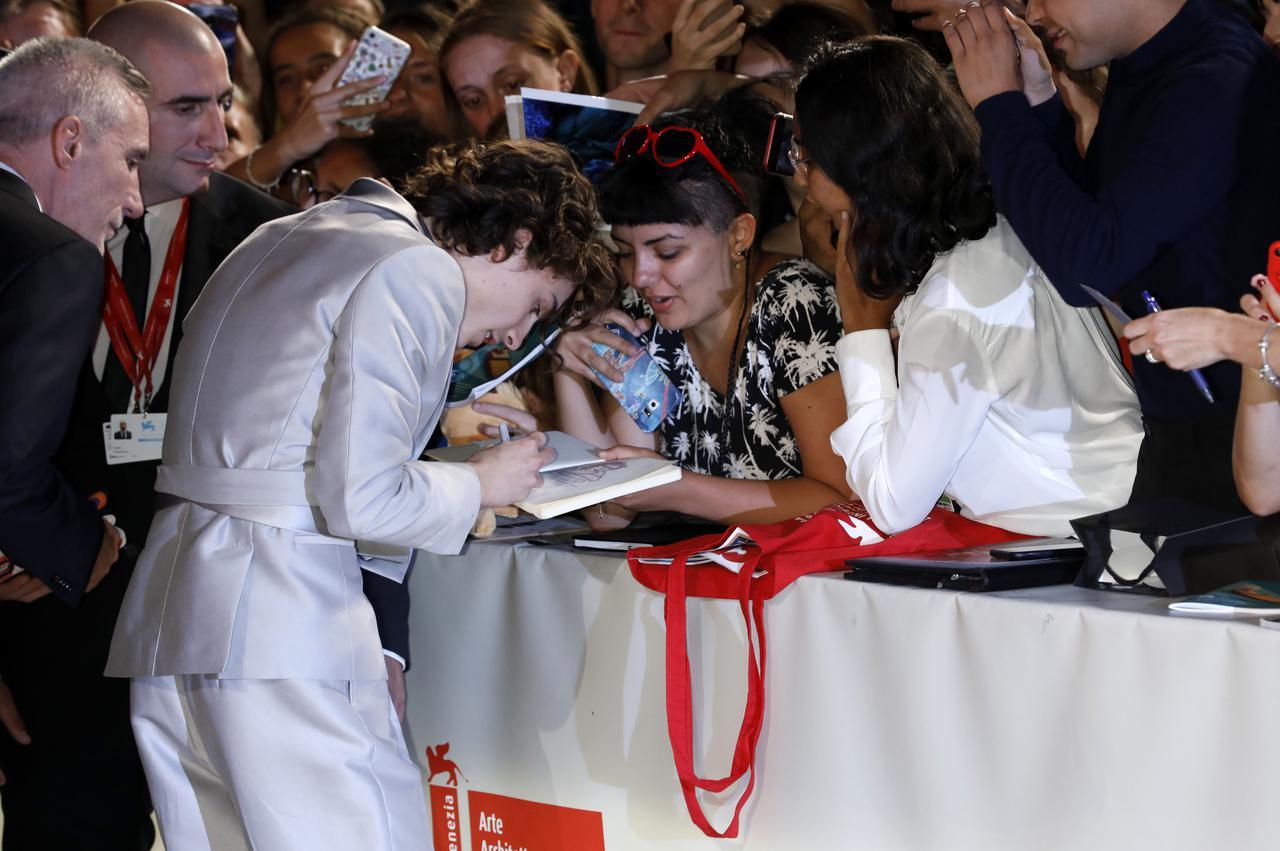 画像: 第76回ヴェネツィア国際映画祭でファンのノートにサインするティモシー・シャラメ。