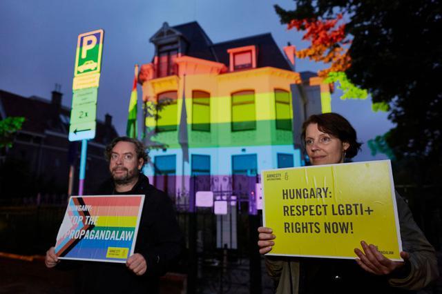 画像: 6月25日、国際人権NGOのアムネスティ・インターナショナルが抗議のために、プロジェクターを使ってオランダのハンガリー大使館を虹色に変えた。