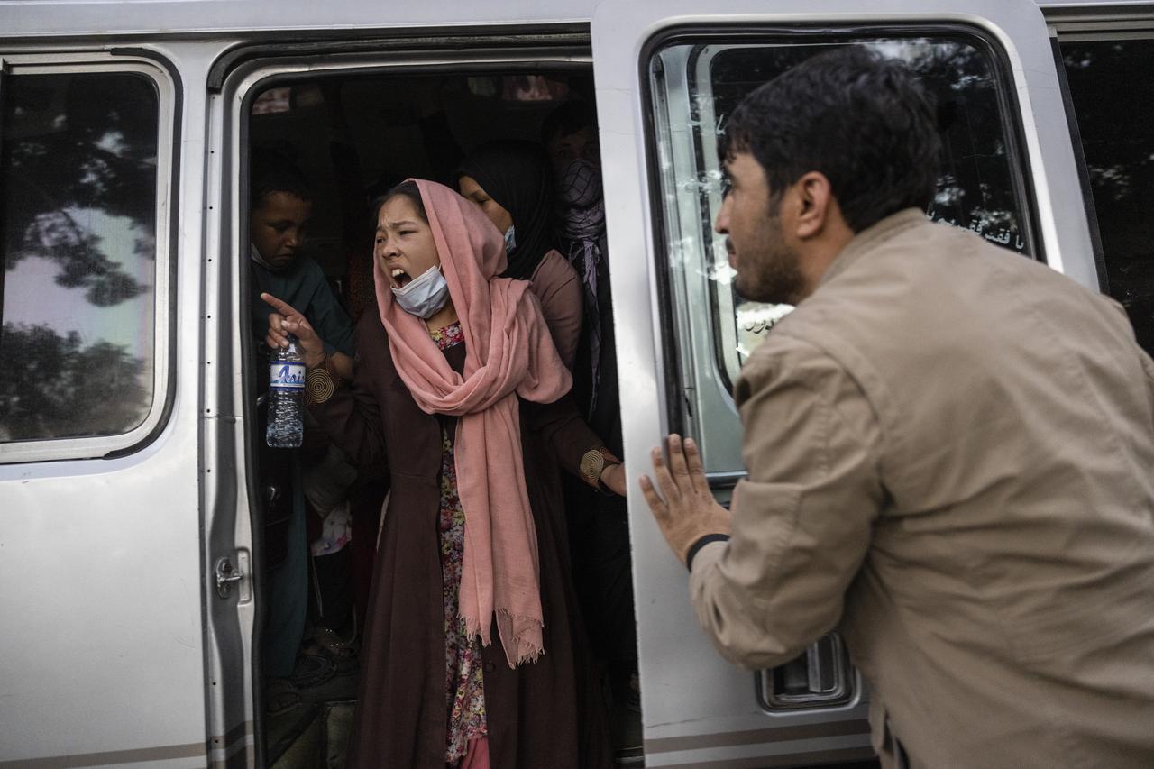 画像: 車から、家族に急ぐよう叫ぶ女性。カブールの国内避難民キャンプから各地のモスクや学校へ移動する人々も多い。(8月12日にカブールで撮影)