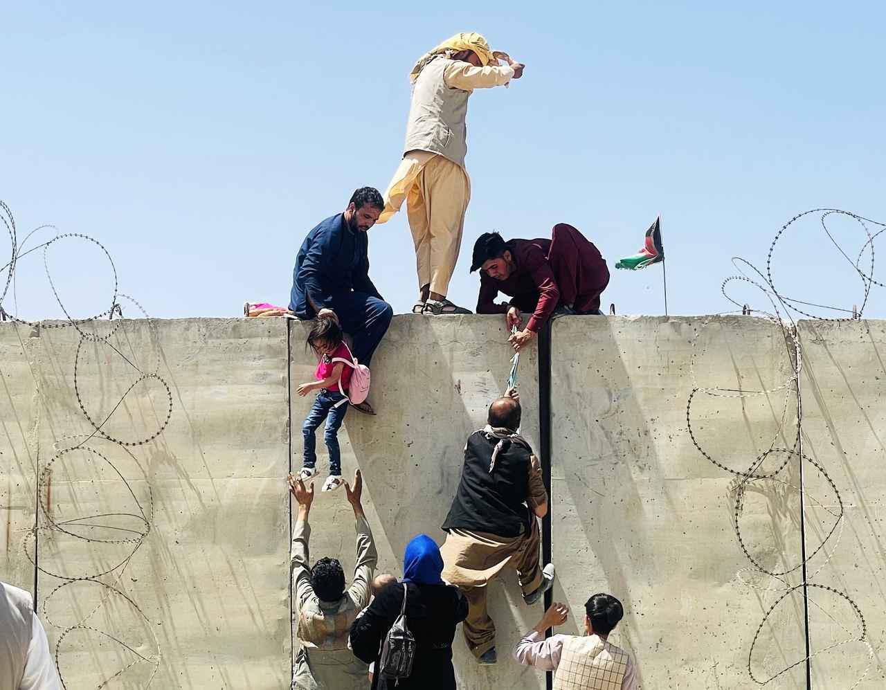 画像: カブール国際空港に入るために塀を乗り越える人々。(8月16日にカブールで撮影)