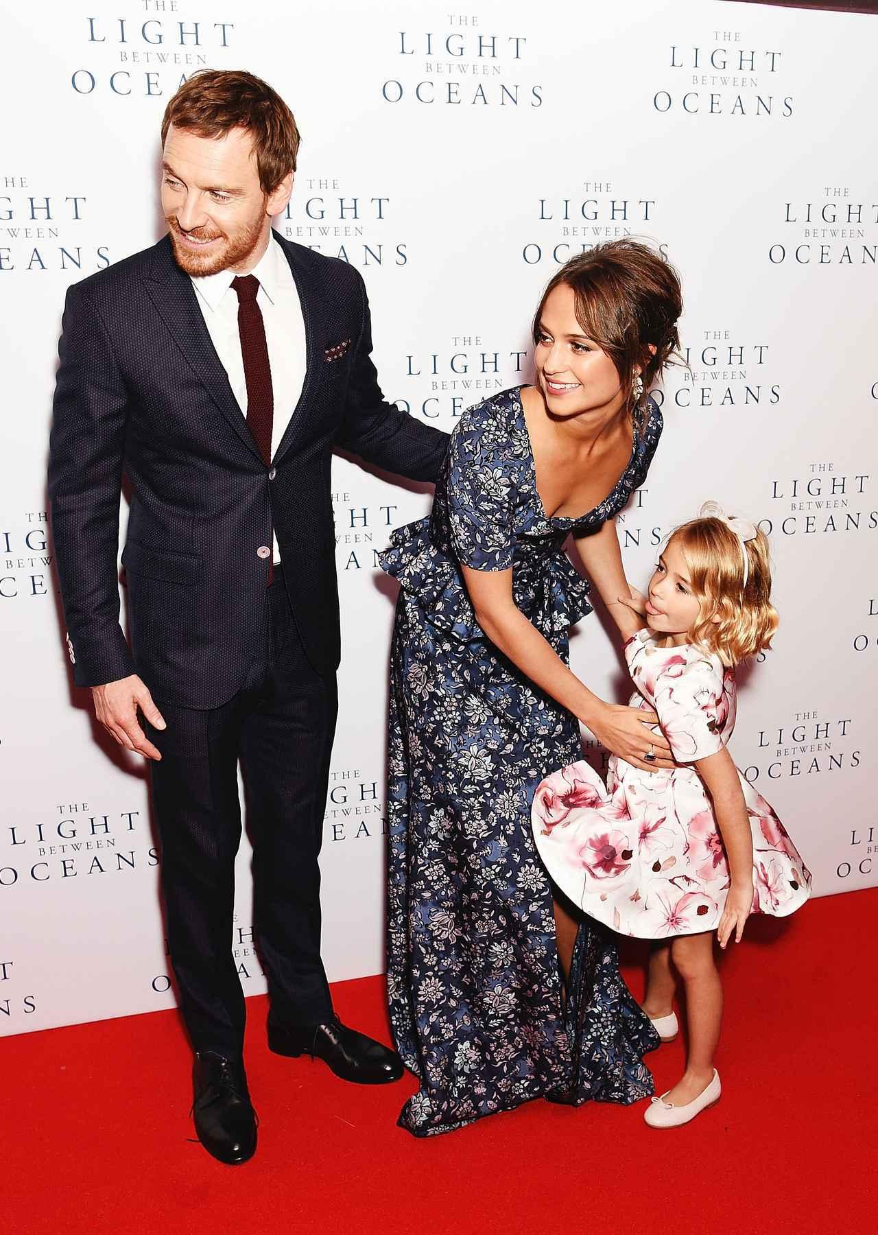 画像: 映画『光をくれた人』のプレミアイベントで、子役とレッドカーペットを歩くマイケル・ファスベンダーとアリシア・ヴィキャンデル。