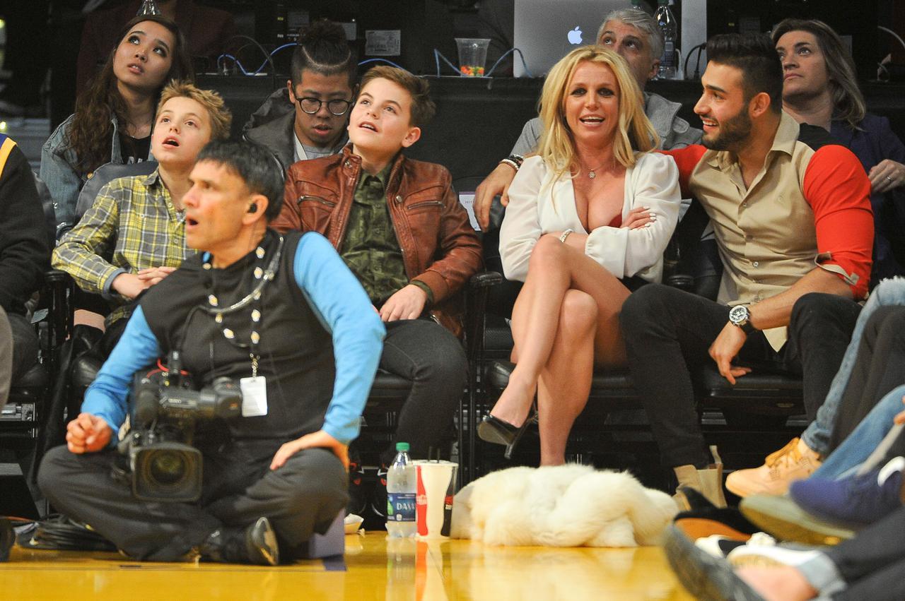 画像: (チェックのシャツを着ている)プレストンと(ブリトニーの左に座っている)ジェイデンと一緒に、ロサンゼルスのステイプルズ・センターでロサンゼルス・レイカーズとゴールデンステート・ウォリアーズの試合を観戦したブリトニー・スピアーズとサム・アスガリ。