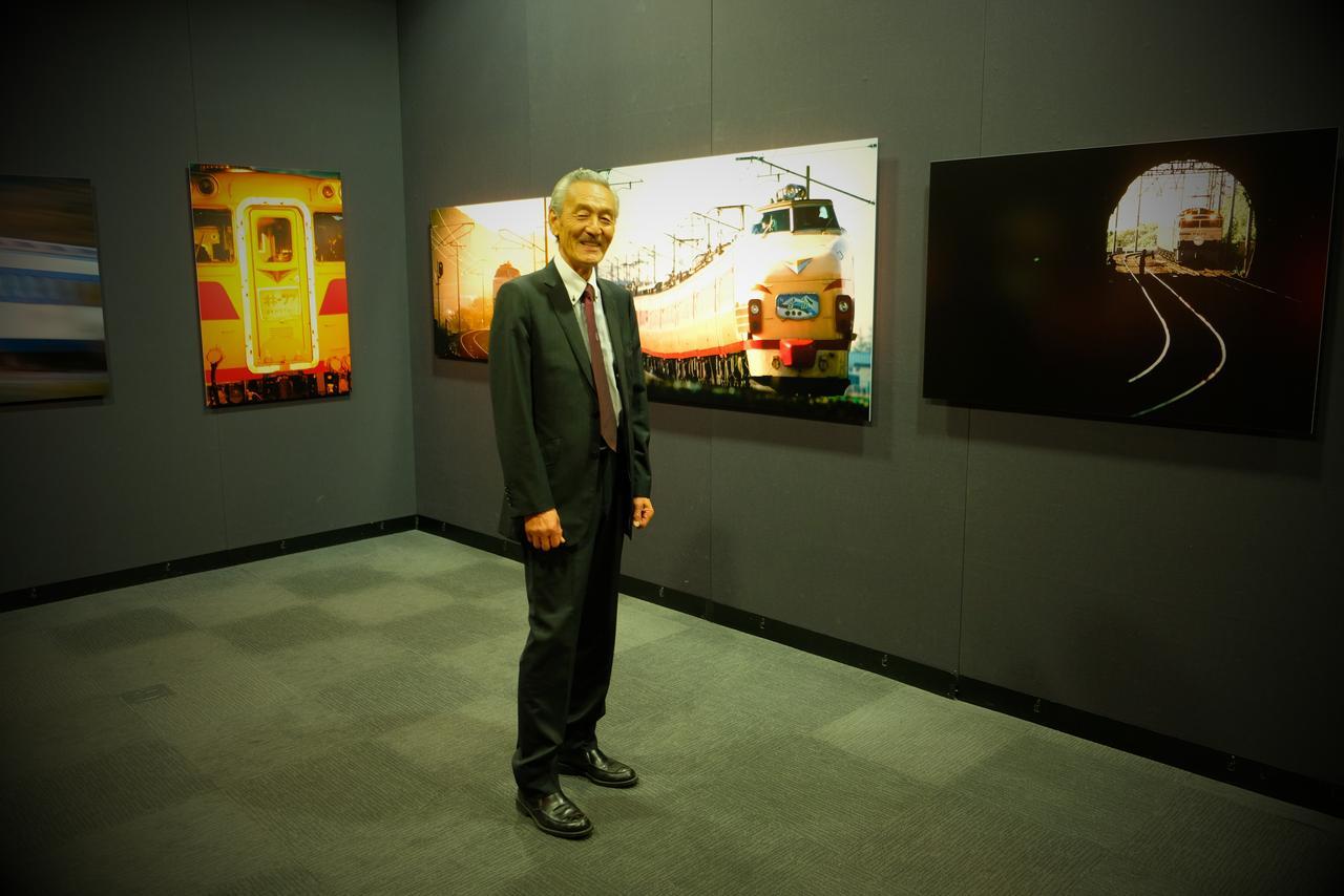 画像: ▲「国鉄カラー」の列車の作品を前にする猪井貴志さん。 cweb.canon.jp