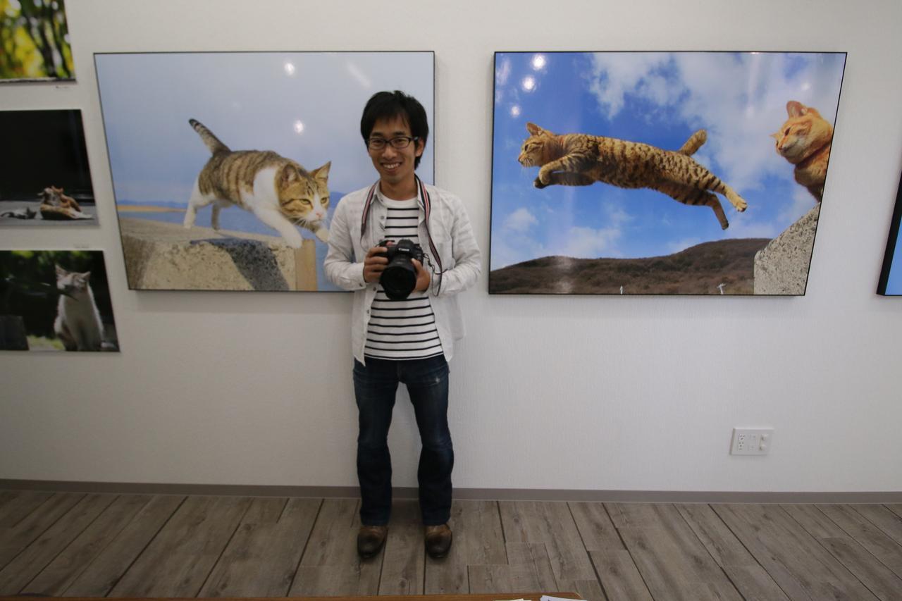 画像: ▲展示作品「飛び猫」を前にする五十嵐健太さん。五十嵐さん猫の写真集「飛び猫」、「フクとまりも」なども同展で購入できる。 k-igarashi.com