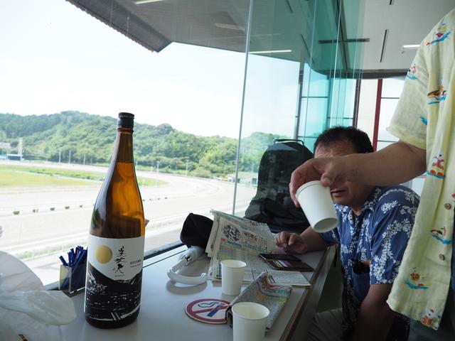 画像: 市内にて買い出し、持ち込んだ一升瓶。コレに加え焼酎のボトルも早々に飲み干し、賭けで負けた2名(すべての行為が賭けの対象となる)が至近のコンビニに走り、さらに酒類を調達。この時の天気はまだイイですね。