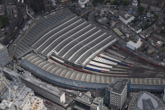 画像: ▲ロンドン市内での空撮。レンズは50-140mm。温室のような風貌の駅はウォータールー駅で、テムズ川の南側に位置し、一時期はユーロスターの発着駅でもあった。ロンドンの街並みは建物のトーンが落ち着いているように感じたので、派手すぎない「アスティア」モードをチョイス。AFモードは「ゾーン」。駅は静物だが乗機の揺れを考慮してシャッター速度は1/2000秒にしている。ちょうど太陽のスポット光が駅に当たり「アスティア」のほどよい発色で柔らかなトーンとなった。 ■XF50-140mmF2.8 R LM OIS WR 絞りF5.6 1/2000秒 ISO500 フィルムシミュレーション:アスティア
