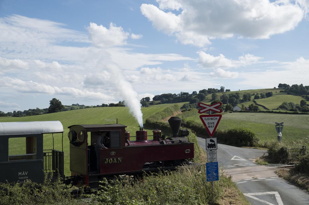 画像: ▲英国ウェールズ地方にある軽便規格の保存鉄道「ウェルシュプール&ランフェア鉄道」。ウェールズらしい牧歌的な丘陵にある踏切を、1927年製のSLがのんびり走る。SLが来る直前、雄大な景色を前に「ベルビア」にいくかどうかと「フィルムシミュレーション」で悩んだが、半逆光気味の状況を考慮し、発色とコントラストが柔らかい「アスティア」をチョイスした。 ■XF18-55mmF2.8-4 R LM OIS 絞りF5 1/1000秒 ISO200 フィルムシミュレーション:アスティア