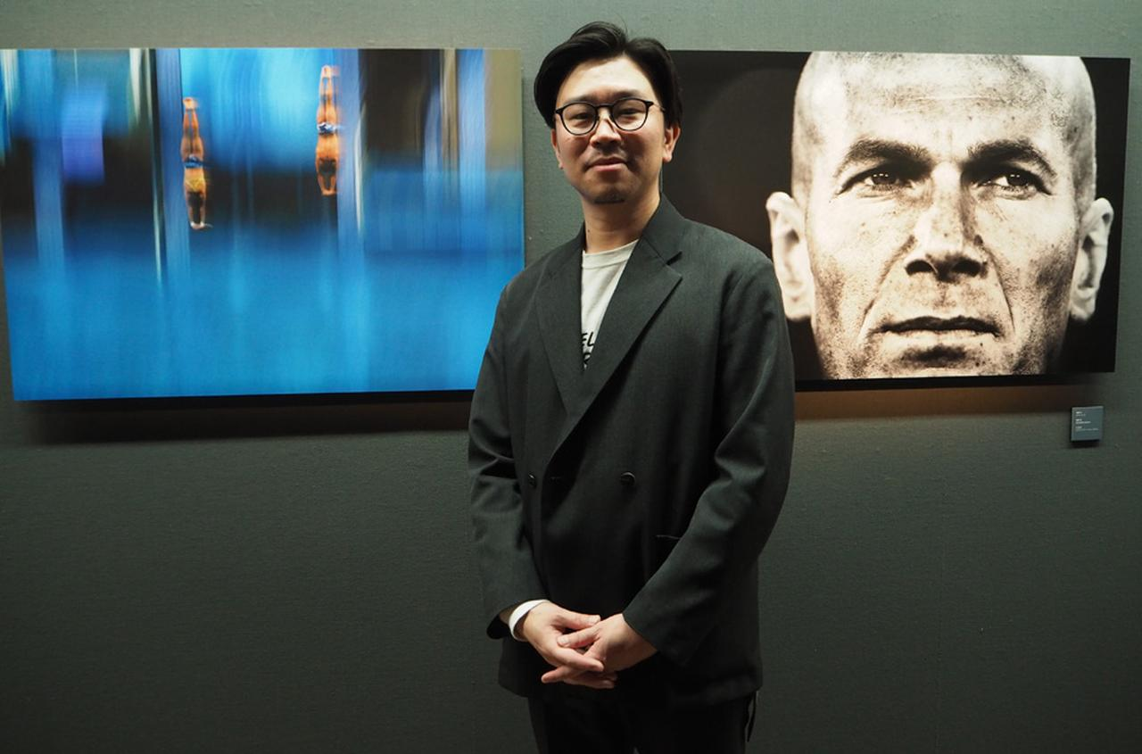 画像: 本日、在廊していた田中伸弥氏。「ジダンの顔のアップの作品は水谷章人先生に褒められたんです。東京五輪に向かってますますスポーツシーンを盛り上げていきたいですね」。写真展のタイトルとなったCALM EYES(落ち着いた目)同様に、話し方も落ち着いている。 cweb.canon.jp
