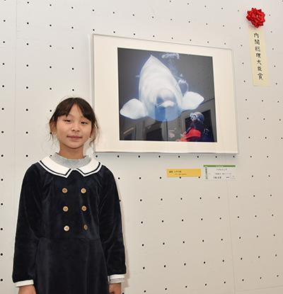画像: 第21回総合写真展で内閣総理大臣賞を受賞した福岡県在住の小学3年生 下條 良菜さん(9歳) ❇︎学年・年齢は受賞当時のものです。 受賞作品「バブルリング」の前で