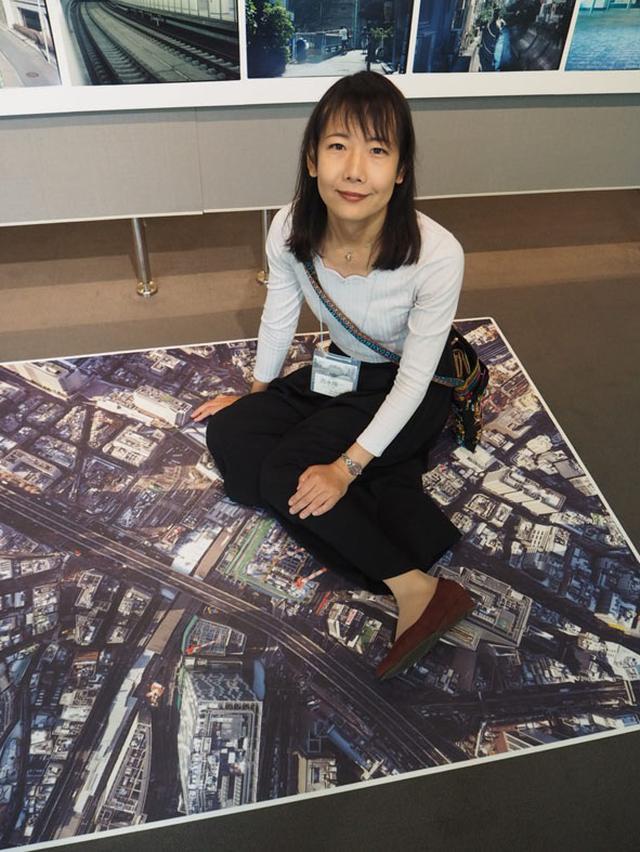 画像: 「空からの眺めを皆さんにも疑似体験してほしい」と、床に貼られた渋谷の俯瞰写真。2010年、2016年、2018年と渋谷の空から撮影した作品を展示しており、激変する都会の街の変遷具合も追える。