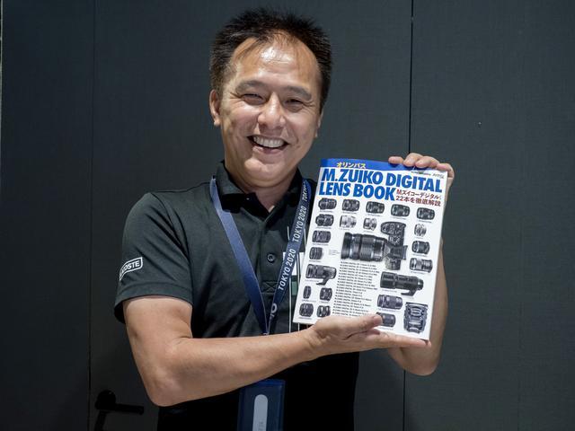 画像: 小城崇史さん。手にしているのは9月28日に発売になったばかりのオリンパスM.ZUIKO DIGITAL LENS BOOK。このムックでは小城さんに執筆いただいています。