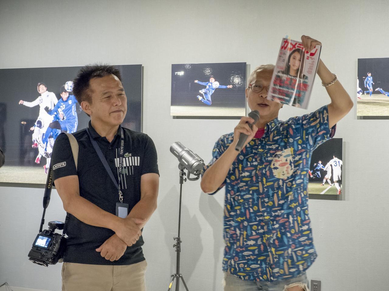 画像: 写真展初日の会場で挨拶をするカメラマン編集部・坂本。坂本が手にしているのはカメラマン10月号で、TOP LIGHTでも小城さんの作品が紹介されています。後ろにみえるのが今回使用したフラッシュ。
