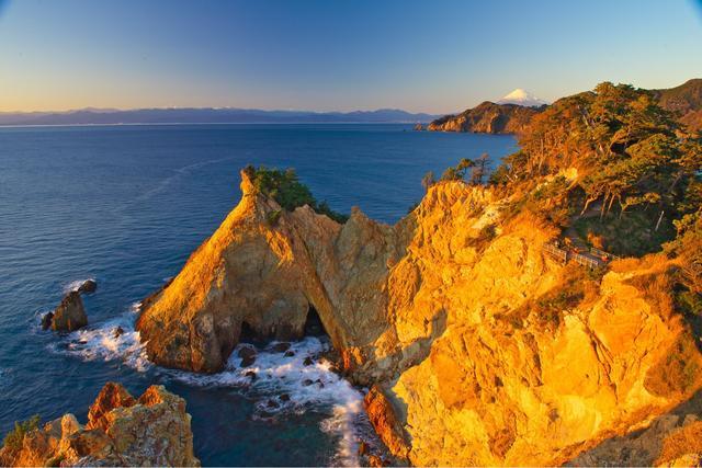 画像: 黄金崎 夕陽を浴びて黄金色に輝く。その形から馬ロックと呼ばれている。
