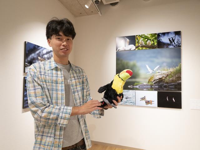 画像: 菅原貴徳さん。菅原さんが手にしているのはサンショクキムネオオハシのぬいぐるみ。残念ながら今回の展示にはこの鳥の写真はないという。