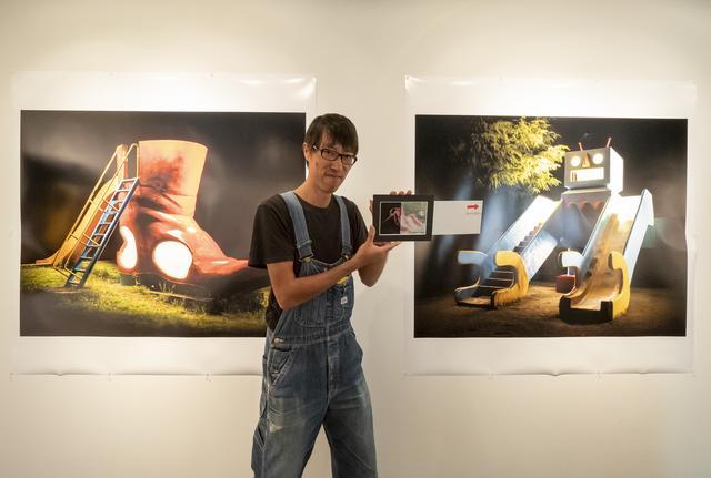 画像: 作者の木藤さん。手にしているのは遊具が昼と夜の姿に変わるなんとも不思議な写真。会場で試せます。