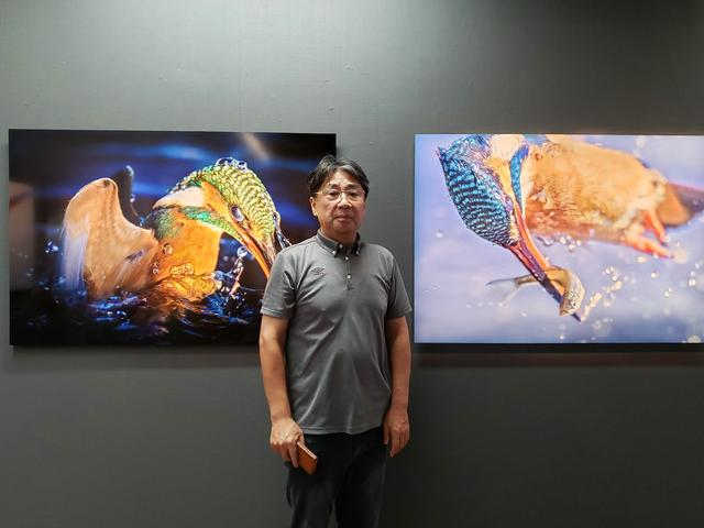 画像: 写真家 小曽納久男さん。翡翠が一瞬一瞬に魅せる美しい形と色を写し撮ることで、野生が生きる力と躍動を感じてもらうことができればと、作品の発表に至ったそうです。