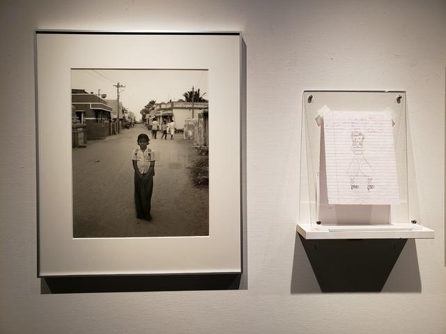 画像: A.Rishaちゃんという少女の写真の横には、彼女が書いた絵とタミル語で書かれたノートの1片が並ぶ。そこには「私はこの村が好き。先生も好き。この村に原子力発電所が立って、危険と隣り合わせになったことは、たくさんの人に影響を与えている。」と書かれている。