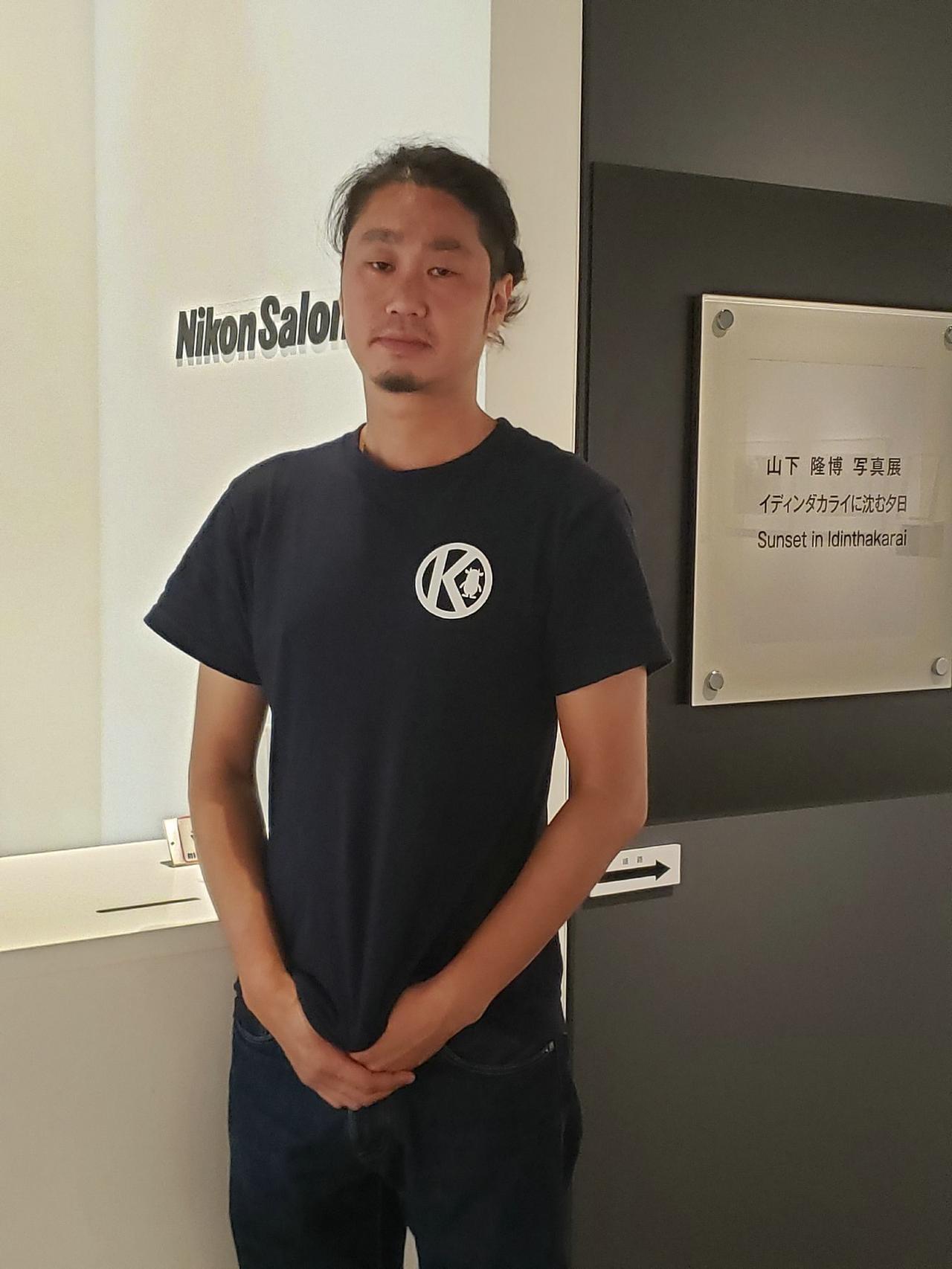 画像: 写真家の山下隆博さん。今日、着ているTシャツは北海道木古内町のご当地Tシャツ。訪れた地のご当地Tシャツを着るのが好きとチャーミングな笑顔を見せてくださった山下さんでした。会場では山下さんのポートフォリオや写真集もご覧いただけます。
