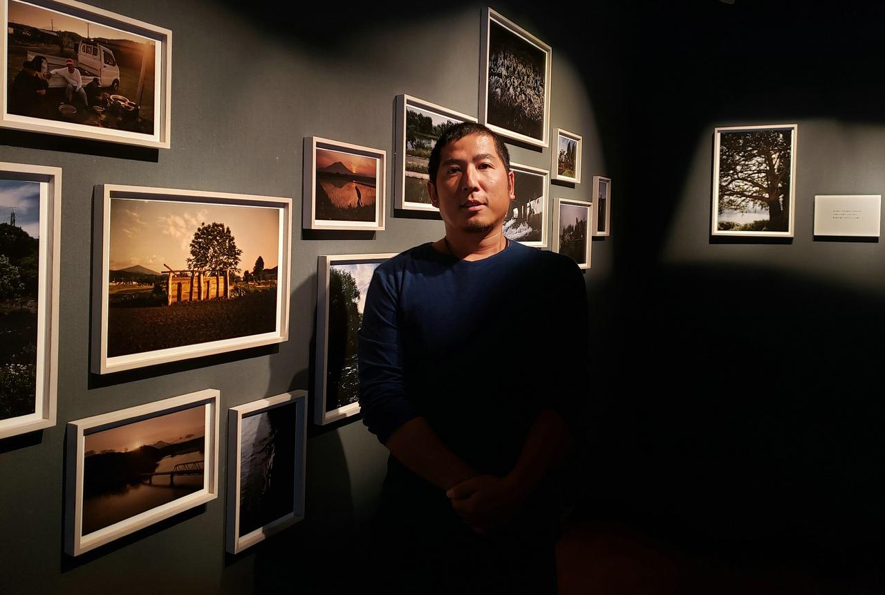 画像: 写真家の公文健太郎さん。 公文さんは「人の営みがつくる風景」をテーマに、国内外で作品を制作。近年は日本全国の農風景を撮影し『耕す人』と題して写真展・写真集にて発表されています。 会場では新刊の写真集『暦川』(2019年・平凡社刊)も販売しています。