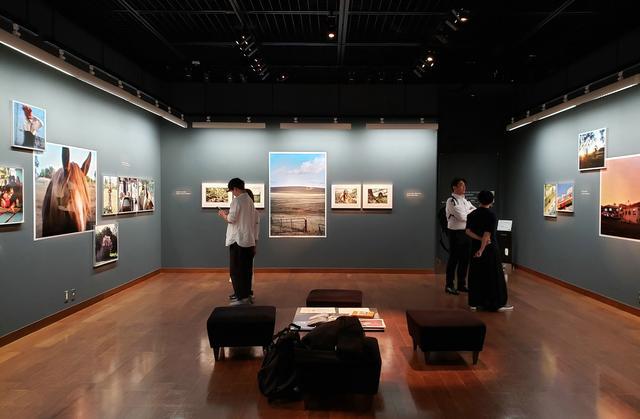 画像: 展示風景。写真展には、初日から多くの方々が訪れ、皆さんが、展示作品を撮影されたり、七咲さんと談笑されたり、作品集などに目を通しながら楽しまれている様子が印象的でした。