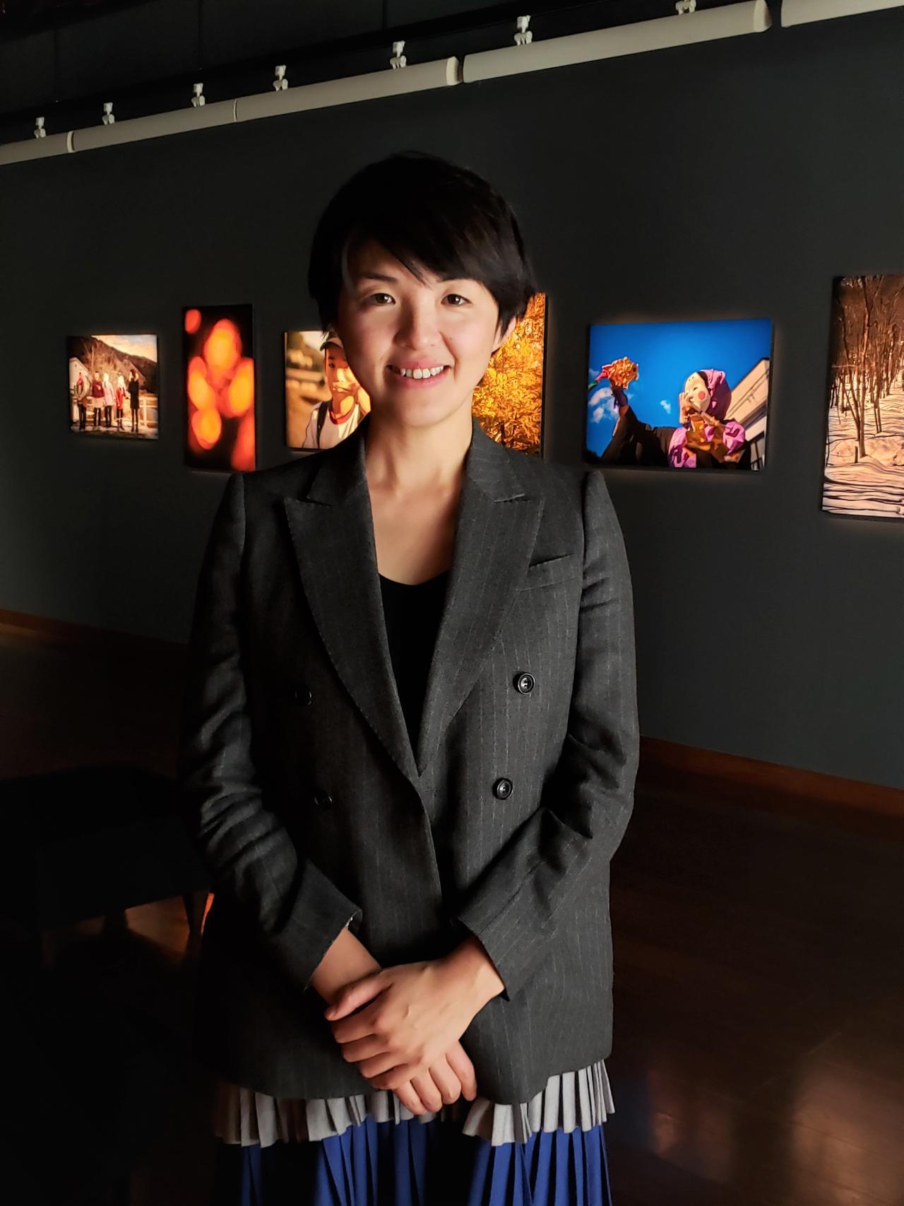 画像: 写真家の田頭真理子さん。写真展に来場される方々が、明るくユーモアいっぱいの田頭さんとお話されていると、皆さん笑顔で楽しそうに写真を鑑賞されていました。