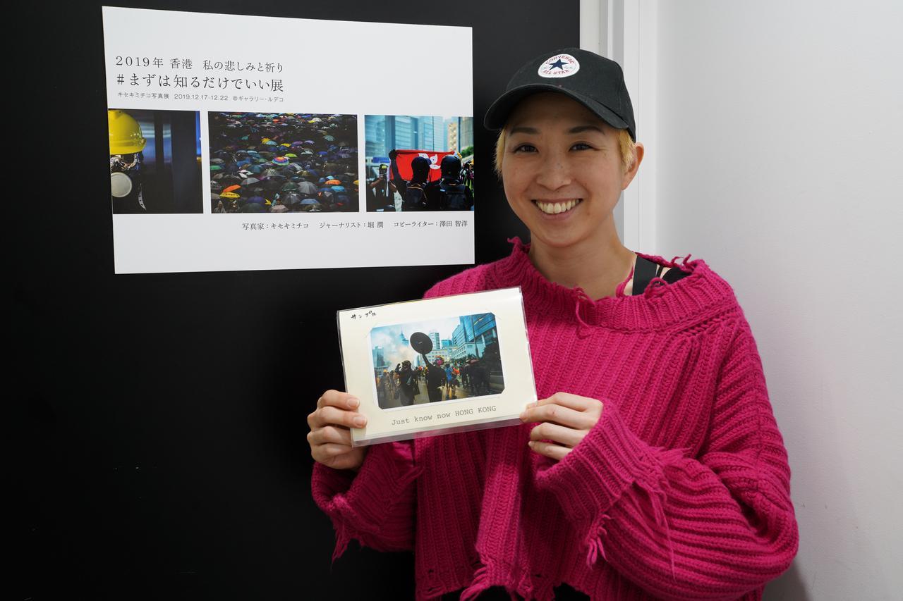 画像: ▲手作りの限定写真集を手にするキセキミチコさん。展示会場では映像作品も上映されている。