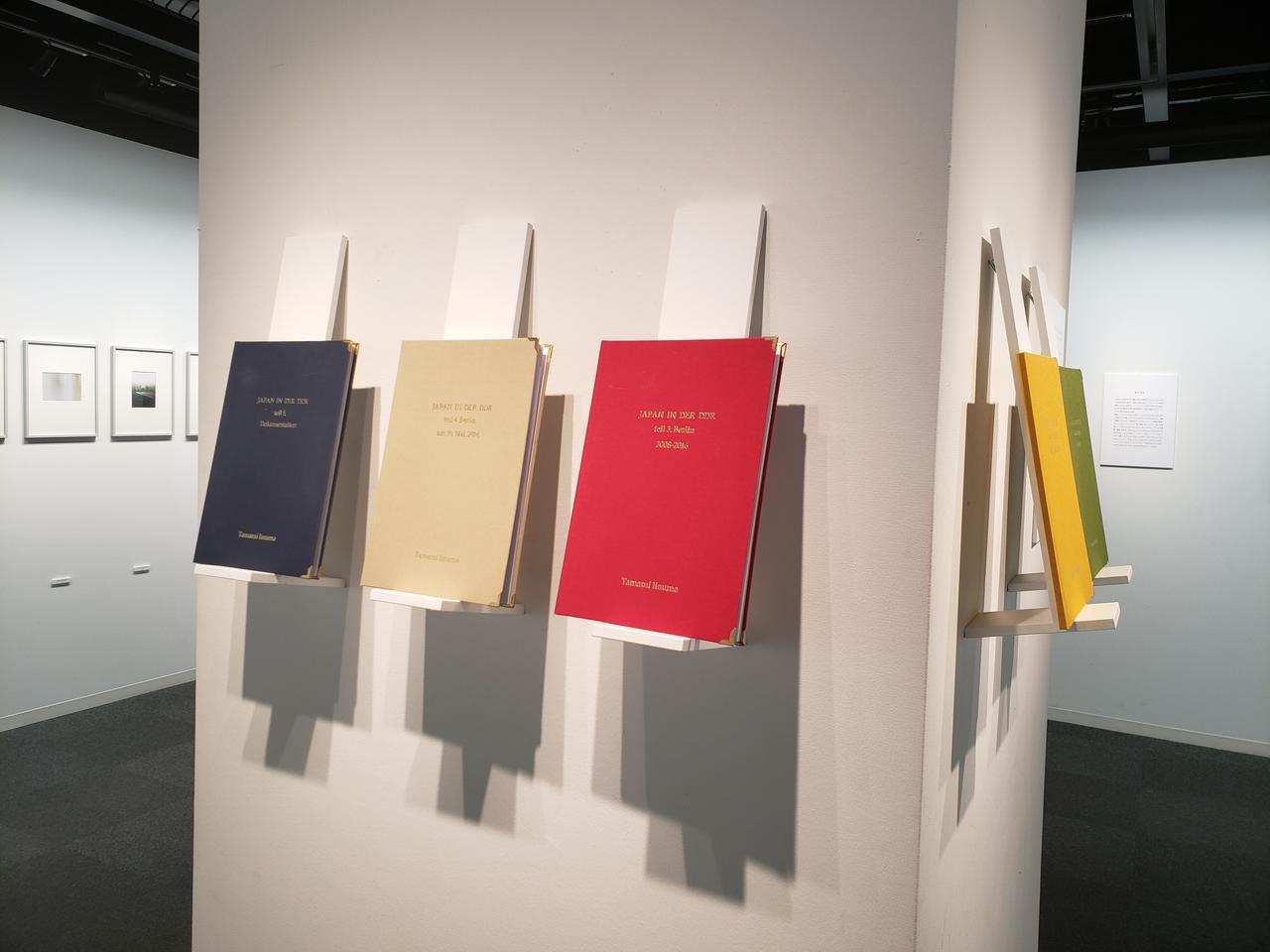画像: 会場では、ドイツのコピーショップで作ったという私家版『JAPAN IN DER DDR 』も展示。この5冊の私家版をまとめた写真集も会場にて販売中です。私家版と今回出版された写真集、本展のDMのデザインは、東京とベルリンを拠点とする高室湧人さんが担当されたそうです。