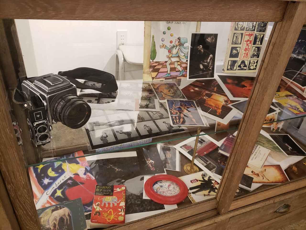 画像: 会場にある古いガラスの飾り棚には、串田さんが撮影に使用したハッセルブラッドやベタ焼きも。 串田さんが大切にされているサーカスを題材にした本や、ルオーやシャガールのポストカードなども一緒に展示されていて、小さな空間の中にもサーカスの幻想的な魅力がたくさん詰まっています。