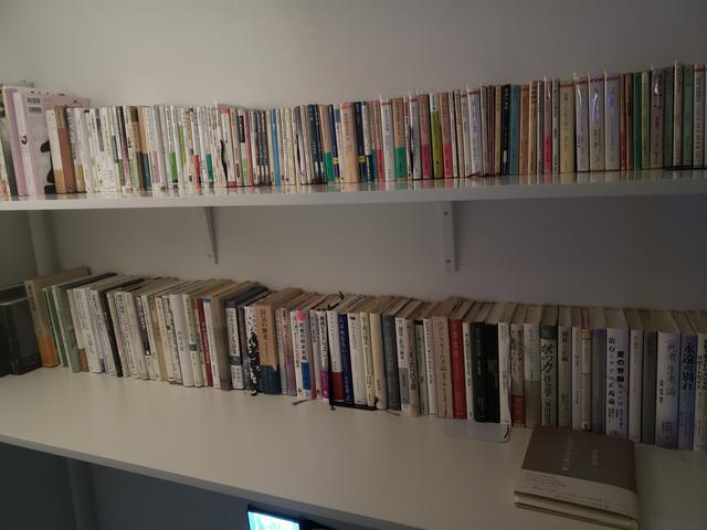 画像: 勝又さんの私物である本も展示されていて、手にとって閲覧することが可能です。本の中には、その本のページに書かれた内容と関連付けた写真が挟まれています。