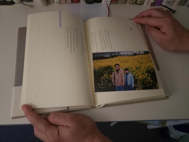 画像: この本(『シャガールと木の葉』谷川俊太郎著、岩波書店)の「願い」と題された詩のページには、一面に咲く黄色い花の前で、雅代さんと旦那さんが一緒に写った写真が挟まれていました。