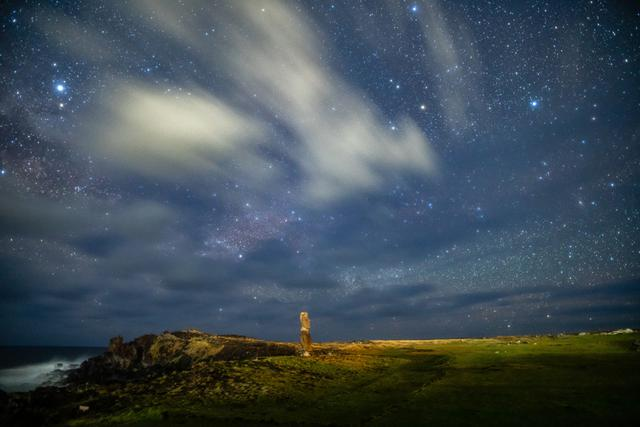 画像: 「ハンガ・キオエ、流れる雲とアルタイル」 ▲島の唯一の町、ハンガロアの近くに立つ単独のモアイだ。街灯りのために雲が白く輝いている。左上に見えている明るい星が日本でもおなじみの彦星・わし座のアルタイルだ。 ■ ソニーα7R III SIGMA 20mm F1.4 DG HSM Art 絞りF1.4 30秒 ISO3200 赤道儀による追尾撮影 Leeソフトフィルター3番