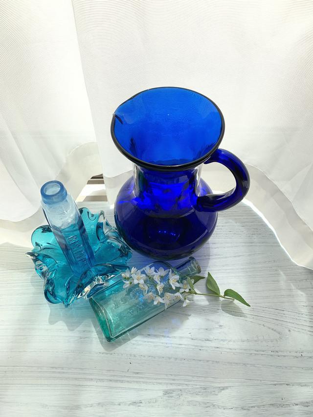 画像: ▲日中、窓からの自然光を使い、色ガラスを並べて青色を作る。瓶の上に花を置き、背景の色、影の色などを使いながらマクロ撮影。実際に撮った時はカーテンを開け、直射光を使って撮影している。