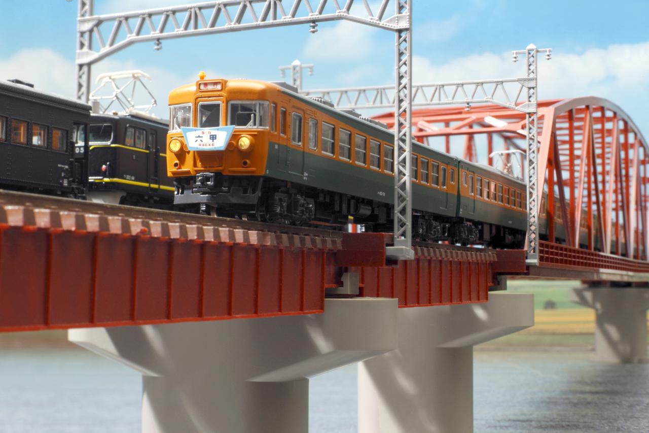画像: ▲往年の急行列車が鉄橋を渡る。川は、表面に細かい凹凸のある透明ビニールシートを敷いているだけで表現している。このように手近な素材を転用することも模型撮影の楽しさのひとつだ。シフトレンズを用いている。 ■キヤノンEOS-1D MarkIV TS-E24mm F3.5L+エクステンダーEF2xII+エクステンションチューブEF12 絞りF32   1/125秒  ISO400 WB:太陽光(ストロボでライティング)
