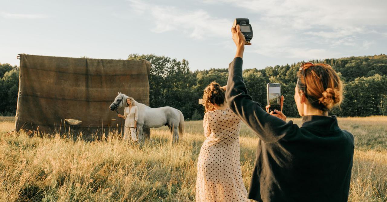 画像: ▲上の作品の撮影状況。被写体に近い女性が一眼レフカメラで撮影し、後方の女性はスマホで操作している。