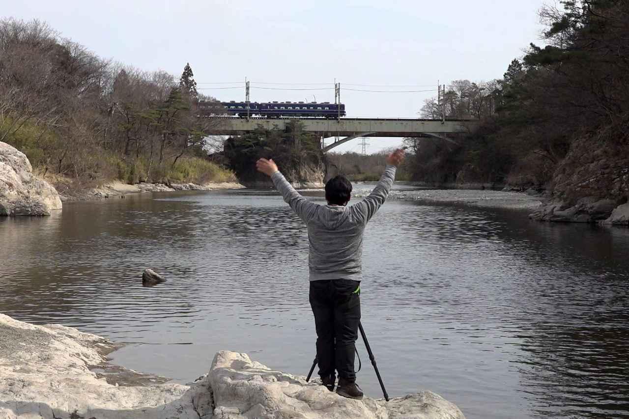 画像: 撮影後にはいつも感謝の気持ちを込めて列車に手を振る助川氏。 鉄道を愛してやまないのだ。