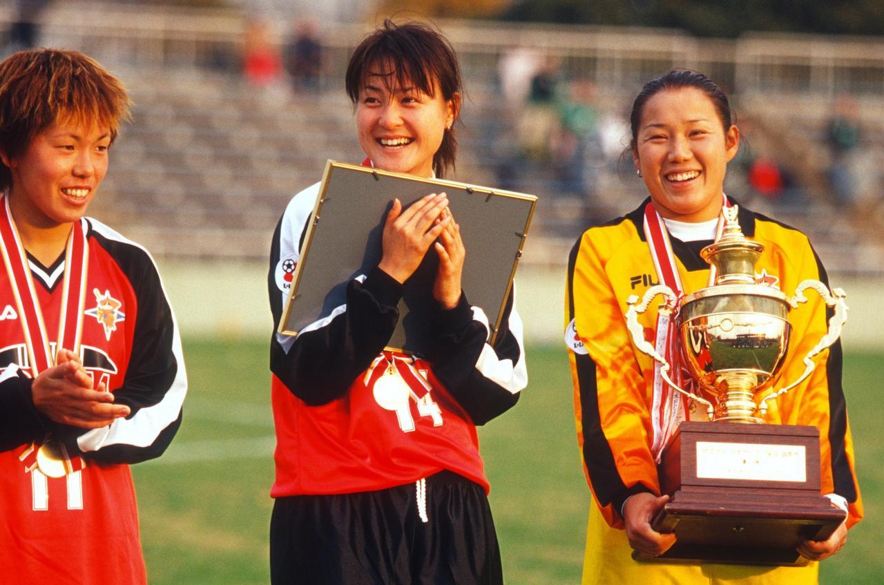 画像: 当時20歳、チーム加入3年目でボランチの主力に定着した宮本さん(中央)が表彰状を手に満面の笑み。その右は、当時ちーうメイトでなでしこジャパンのGKでも活躍した山郷のぞみさん(現・ASエルフェン埼玉のGKコーチ)