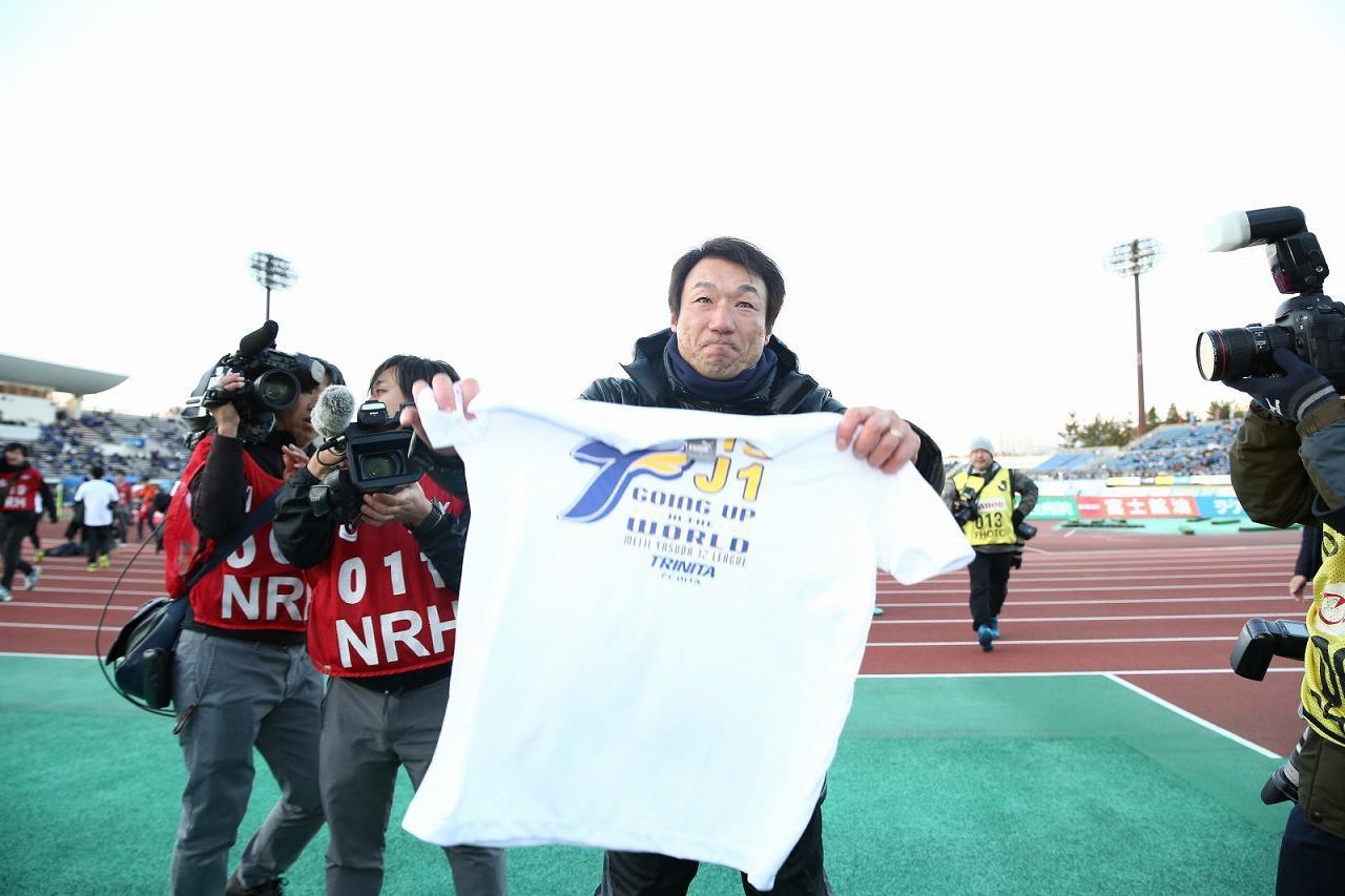 Images : 1番目の画像 - 試合後、片野坂監督がJ1昇格の記念Tシャツをスタンドのサポーターに向けて掲げる 写真◎J.LEAGUE PHOTOS - ベースボール・マガジン社WEB