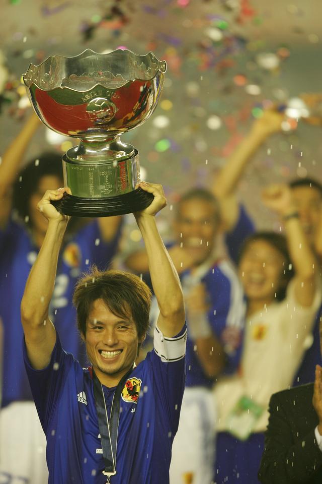 画像: 日本の選手たちの水のシャワーが舞う中、優勝カップを高々と掲げる宮本。この後にジーコ監督にカップを渡そうとした宮本に、指揮官は「それは君たちのものだ」と答え、自らは掲げなかった(写真◎BBM)