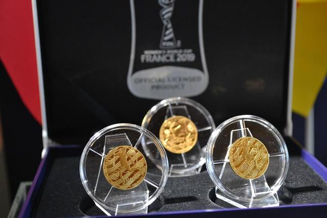画像: 金貨は3種類で、オモテ面にはトロフィーと過去の優勝国の国旗が、裏面には女子選手がボレー、ドリブル、ヒールトラップをダイナミックにプレーする瞬間がダイナミックに描かれている