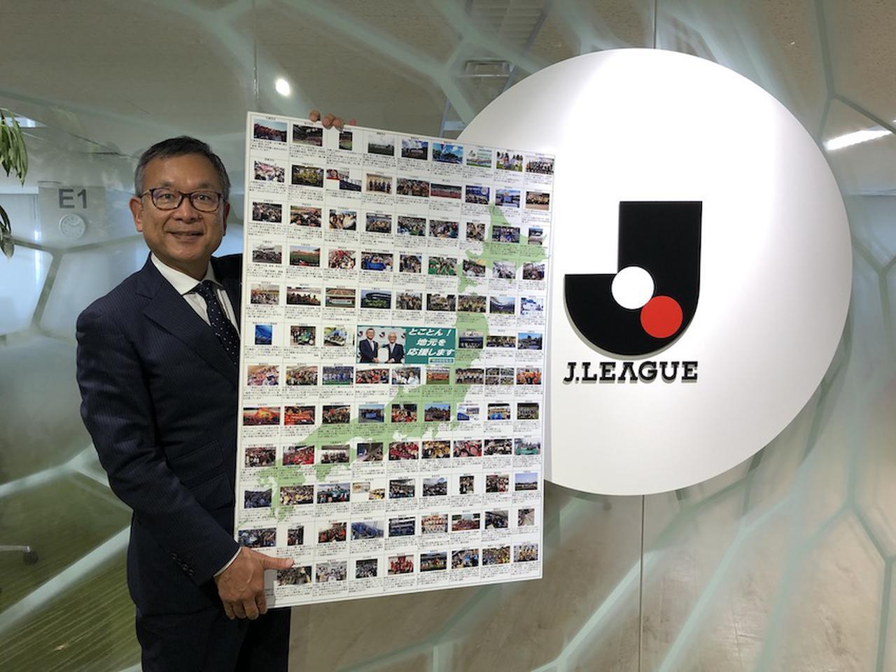 画像: 明治安田生命から贈られた「Jリーグ頑張ってください」というメッセージ入りボードを手にするJリーグの村井満チェアマン
