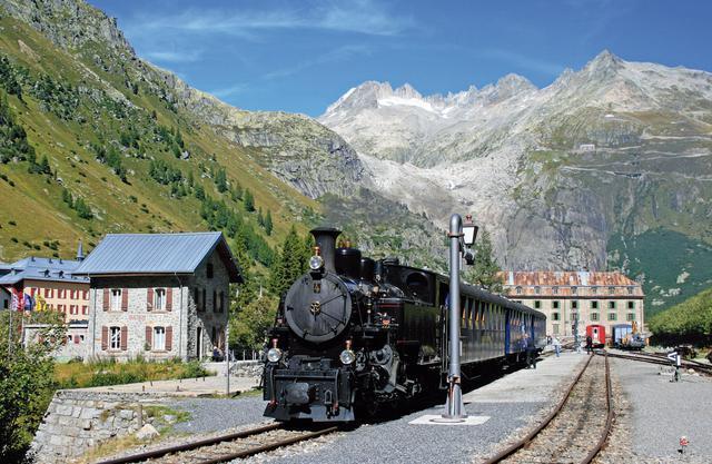 画像: フルカ山岳蒸気鉄道の背後にはローヌ氷河が見える