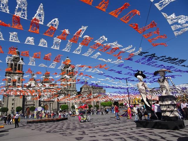 画像: 首都メキシコシティのソカロも「死者の日」一色です 大人気ハリウッド映画のオープニングで使わたことでも有名です 頭上には伝統手工芸品のカラフルな切り紙「パペルピカド」