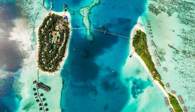 画像: 橋で繋がれたコンラッド・モルディブ。橋の中央部あたりに水上飛行機が発着する。右側の小さな島には水上コテージやレストランが、左の大きな島にはビーチコテージやプール、レストラン、スパなど主な施設が並ぶ。