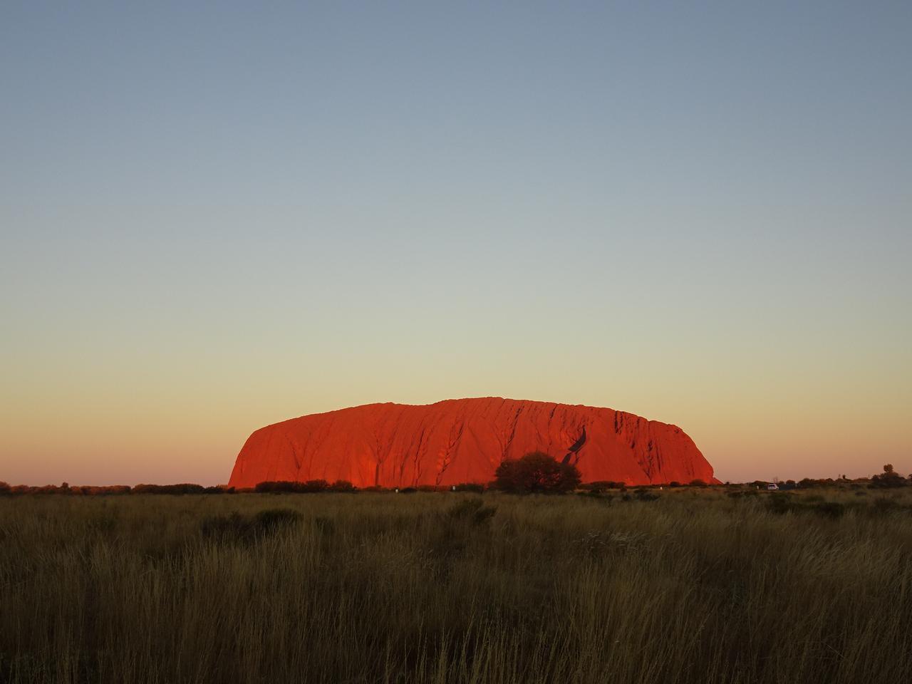 画像: 夕日に照らされ燃えるような赤に染まるエアーズロック